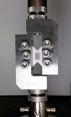 image of a tensile test instrument with a rail shear fixture and speciemn installed.